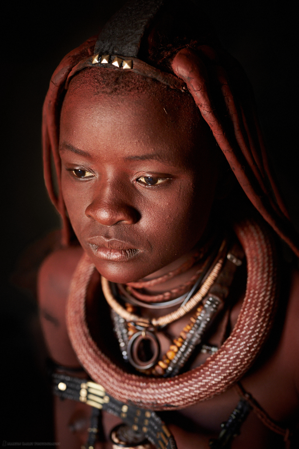 A young Himba lady caught in a moment of thought